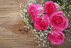 Rosas y Gypsophila rosados en fondo de madera Imagenes de archivo