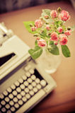 Rosas y máquina de escribir vieja Foto de archivo libre de regalías
