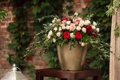 Rosas y peons en florero en el primer de la tabla Fotografía de archivo