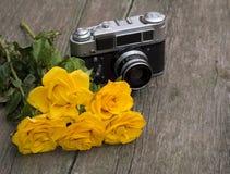 Rosas y retro amarillos la cámara detrás de ellos en una tabla Imagenes de archivo