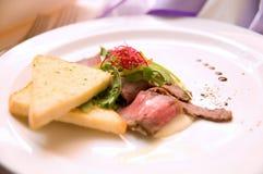 Rosbif y tostada con arugula en la placa blanca Imagen de archivo