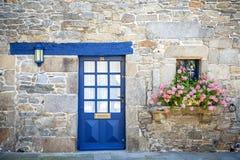 Roscoff Traditioneel Frans steenhuis met blauwe die deur en venster met rode bloemen in Roscoff, Bretagne, Frankrijk wordt verfra royalty-vrije stock fotografie