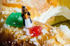 Roscon de reyes and one wise men figurine Baltasar. Detail on a kings cake and a figurine that can be found hidden into it. Roscon de reyes or rosca de reyes Royalty Free Stock Photos