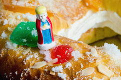 Roscon de reyes and one wise men figurine Melchor. Detail on a kings cake and a figurine that can be found hidden into it. Roscon de reyes or rosca de reyes with Stock Photo