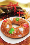 Roscon de reyes, spanish three kings cake. A roscon de reyes, spanish three kings cake eaten on epiphany day, and a pile of gifts Royalty Free Stock Photos