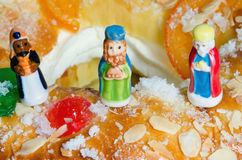 Roscon de reyes and three wise men figurines. Detail on a kings cake and three figurines that can be found hidden into it. Roscon de reyes or rosca de reyes with Stock Images
