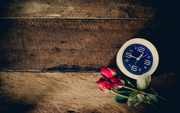 Rose and alarm clock on wooden background stock photography