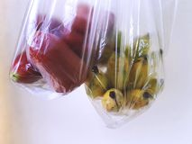 Fresh Rose Apples and Ripe Bananas in Transparent Plastic Bags royalty free stock photography