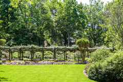 Rose Arbor Over Green Grass. Beautiful landscaping in a lush, green public garden Royalty Free Stock Images