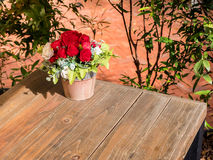 Rose artificial flowers in the pot , on the wood desk Stock Photos