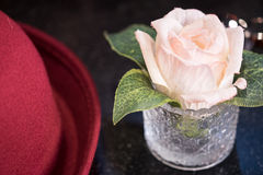 Rose artificielle rose dans l'endroit en verre près du chapeau rouge Image libre de droits