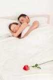 Rose auf einem Bett der Schlafenpaare Lizenzfreie Stockfotos