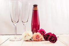 Rose auf Holzfußboden mit Champagne und Glas Lizenzfreie Stockfotos