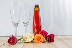 Rose auf Holzfußboden mit Champagne und Glas Stockbild