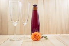 Rose auf Holzfußboden mit Champagne und Glas Lizenzfreie Stockbilder