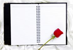 Rose auf unbelegtem Notizblock lizenzfreie stockfotos