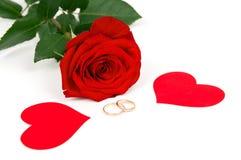 Rose avec des coeurs et des anneaux de mariage Photographie stock