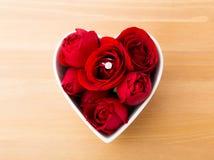 Rose avec la bague à diamant à l'intérieur de la cuvette de forme de coeur Photographie stock