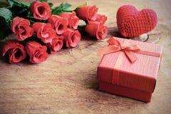 Rose avec le boîte-cadeau rouge et le coeur rouge forment sur la table en bois Image stock
