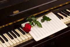 Rose avec le papier de notes sur le piano Photographie stock libre de droits