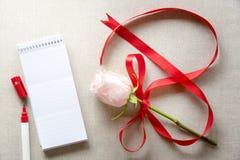 Rose avec le ruban dans la forme de 8 et un carnet Image stock