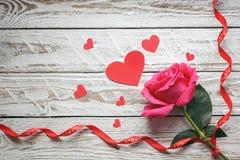 Rose avec les coeurs de papier rouges et ruban sur le fond en bois blanc Concept de symbole d'amour Image stock