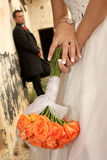 Rose Background. A bride holding roses with groom in background Royalty Free Stock Images