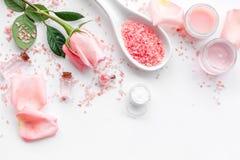Rose bath salt in spoon near rose petals on white background top view copyspace. Rose bath salt in spoon near rose petals on white background top view stock photos
