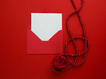 Rose, beads and greeting-card in an envelope on red background. Flat lay Royalty Free Stock Images