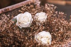 Rose bianche con la merce nel carrello marrone dell'erba del fiore Fotografia Stock