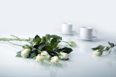 Rose bianche e due tazze bianche fotografia stock