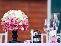 Rose blüht Blumenstrauß mit kleinem Eiffelturm auf einer Hochzeitstafel Lizenzfreies Stockfoto