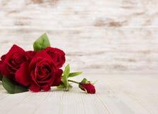 Rose blüht, rot auf hölzernem Schmutzhintergrund, Blumenkarte Stockbild