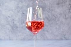 Rose Blush Wine rosa di versamento a vetro Immagine Stock