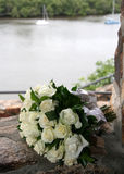 Rose Bouquet. A bouquet of white roses resting on a rock wall overlooking a river Stock Image