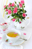 Rose bouquet and cup of tea royalty free stock photo