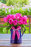 Rose bouquet enamel jug bow. Bouquet of pink roses in a blue enamel jug with a bow of pink ribbon outdoors, copy space royalty free stock photo