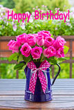 Rose bouquet text happy birthday. Bouquet of pink roses in a blue enamel jug with a bow of pink ribbon outdoors, text, happy birthday royalty free stock photography