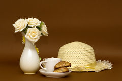 Rose bouquet in a vase, straw hat and coffee with biscotti Stock Photos
