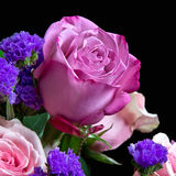 Rose Bouquet. View of a bouquet of roses and purple statice, with focus on one pink rose Royalty Free Stock Photo