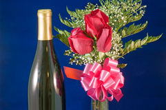 Rose bouquet and wine. A detailed view of three red roses in a bouquet with a pink bow and bottle of wine against a velvet blue background Royalty Free Stock Photography