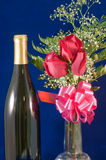 Rose bouquet and wine. A detailed view of three red roses in a bouquet with a pink bow and bottle of wine against a velvet blue background Stock Images