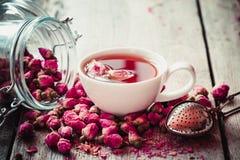 Rose bourgeonne le thé, la tasse de thé, le tamis et le pot en verre avec des boutons de rose Photos libres de droits
