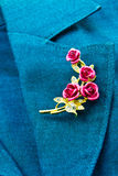 Rose brooch. On a business female suit of blue color Stock Photos