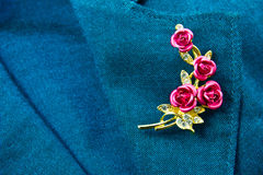 Rose brooch. On a business female suit of blue color Royalty Free Stock Photography