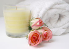 Rose bud bathroom. Delicate pink rose buds and white  clean towel with relaxing candle Royalty Free Stock Images