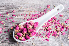 Rose buds in ceramic spoon on old wooden background Royalty Free Stock Images