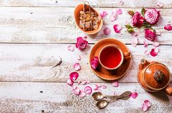 Rose buds tea in a cup. Flowers and tea pot on white wooden table, top view royalty free stock photography