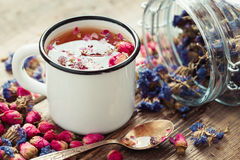 Rose buds tea in tea cup and glass jar of forget me not flowers. Royalty Free Stock Photography