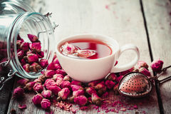 Rose buds tea, tea cup, strainer and glass jar with rosebuds. Selective focus Royalty Free Stock Photos
